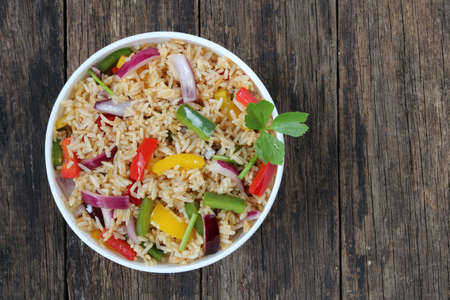 Fried rice with sweet pepper on old wooden background.Top view