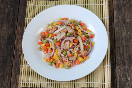 Tuna salad with vegetables on wooden background.Homemade meal for good health and weight loss