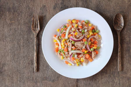 Tuna salad with vegetables on wooden background top view.Homemade meal for good health and weight loss