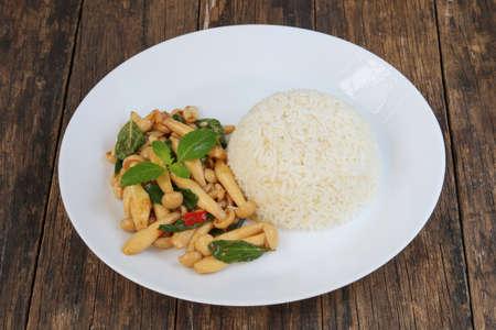 Thai food,stir fried shimeji mushroom with basil and steamed rice on old wood background.This popular Thai dish.
