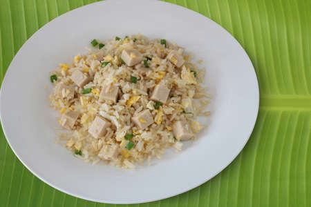 Fried rice with white pork sausage and egg isolated on banana leaf.