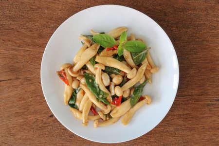 Thai food,stir fried shimeji mushroom with basil on wood background.This popular Thai dish serve with steamed rice.