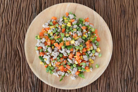 Minced pork salad with vegetables in wood dish.Homemade meal for good health. Archivio Fotografico