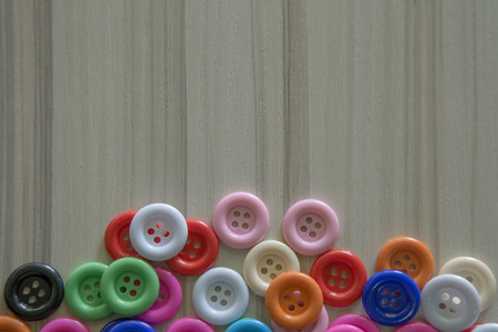 A Multi colored buttons on light wood table Stock Photo