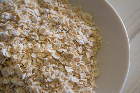 The oats rice in white bowl on top table wood worm tone image Stock Photo