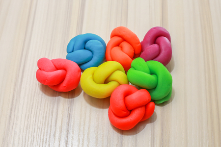 The colorful playdough close up image on wooden table.