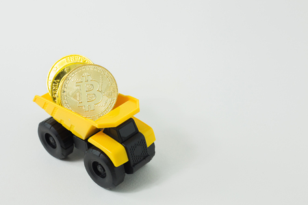 The yellow dump truck toy  isolated bitcoin concept  on white background. Stock Photo