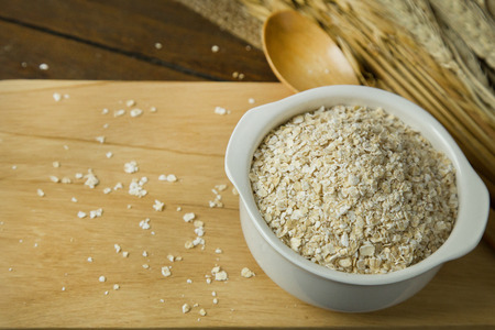Healthy breakfast cereal oat flakes in bowl on wooden table.