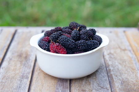 mulberry fruit in white bowl on wood table.