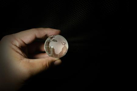 glass ball planet earth and hand image.