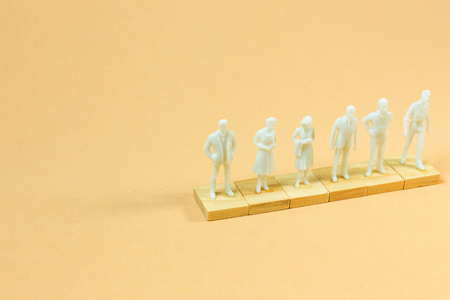 The  white  figure miniature on orange pastel for business content. Stockfoto