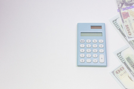 The blue calculator and banknotes on white back ground.