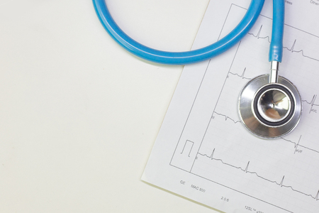 A Blue stethoscopes and  Electrocardiography  chart close up image.
