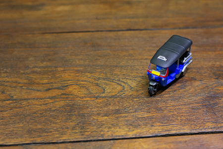 The tuk tuk taxi  toy  on wood table close up image. Stock Photo
