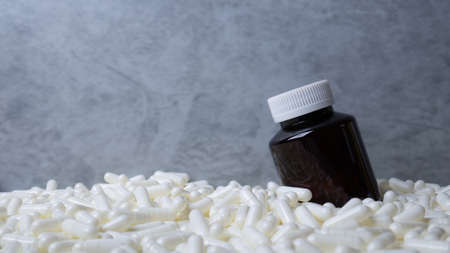 Medicine bottle  and white capsules image  for  sci or medical content.
