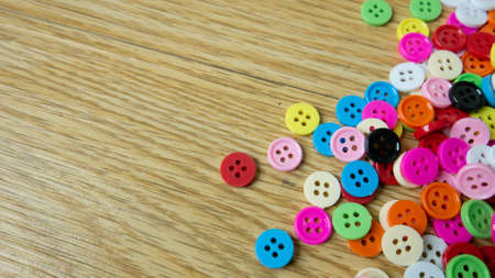 button multicolour  on wood table for background concept