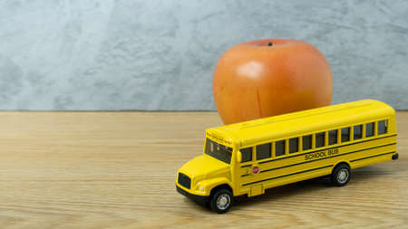 school bus toy and apple on wood table for back to school or education concept
