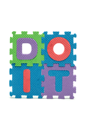 Word DOIT formed with colorful foam puzzle mat isolated on white background photo