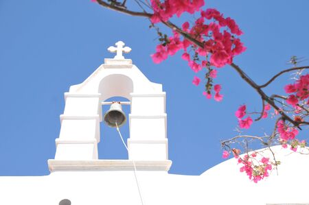 church bell: Church Bell and pink flowers in Mykonos Greece Stock Photo