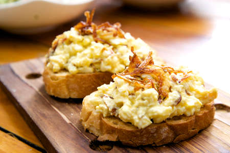 bread slice: Slice of bread topped with egg mayonnaise and fried onion