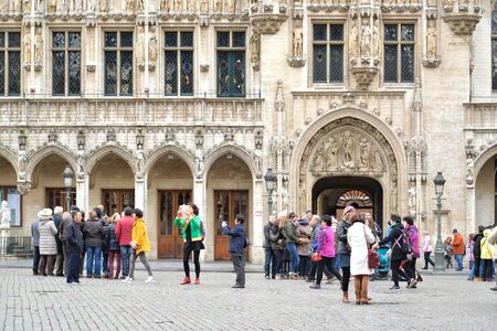 tourist guide: Groups of Tourists are gathering in front of  Brussel town hall to listen to tourist guide and taking pictures, Brussels market square, Belgium. Editorial