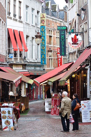 what to eat: A couple decided what to eat in front of small alley with many restaurants in Brussels, Belgium
