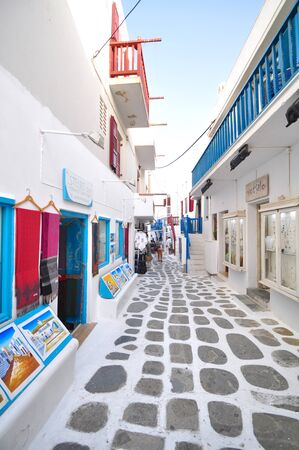 neckless: Tourist is walking in a small alley and looking at souvenir shop along the way in Mykonos city, Greece Editorial