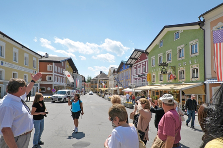 tour guide: Local tour guide brings tourists to visit Mondsee city in Salzburg, Austria.