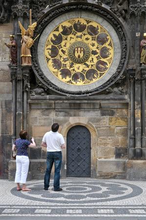 czech women: Tourists are looking at calendar plate at clock tower, Prague, Czech Republic