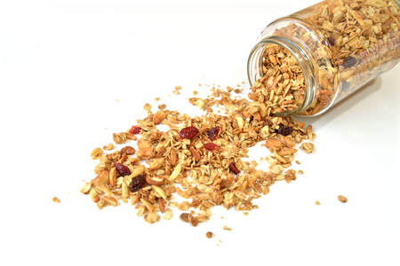 Granola with honey, oatmeal, cashew nut, almond, raisin and cranberry on white background