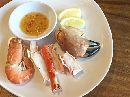 seafood platter: Seafood platter. Shrimp, king crab, French brown crab on white plate with lemon and chilli sauce