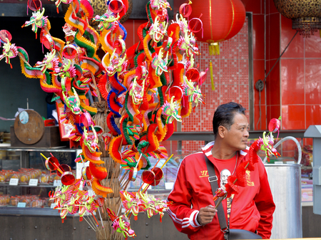 local festivals: A man selling dragon folded paper toy is looking for customers at Chinese New Year festival 2016, Chinatown, Bangkok, Thailand.