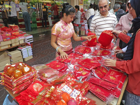 local festivals: A woman is selling traditional red envelopes and red bags to customers at Chinese New Year festival 2016, Chinatown, Bangkok, Thailand. Editorial