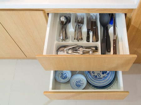 Open drawer with cutlery and dishware in the kitchen