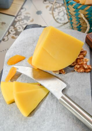 edam: Edam cheese with knife and dried fruit and walnut