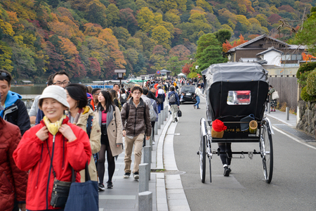 Many tourist walking along the street leads to Togetsukyo Bridge in Kyoto, Japan