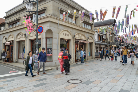 Kawagoe, Japan - May 14, 2017: Many tourists and local people are walking along shops and stores in Kawagoe with the street decorated with Koinobori for children day, Kawagoe, Japan
