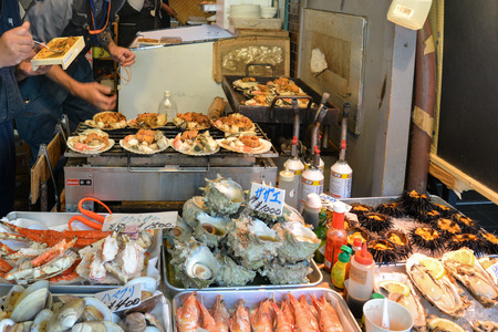 한 남자가 일본 최대의 어시장 인 츠키지 수산 시장에서 다양한 해산물을 굽고있다.