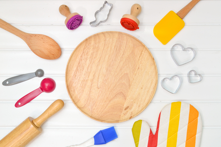 Baking utensils with wooden plate from top view