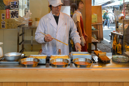 Tokyo, Japan - May 16, 2017: A man is making Tamagoyaki, Japanese rolled omelette, along the street at Tsukiji fish market, Tokyo, Japan