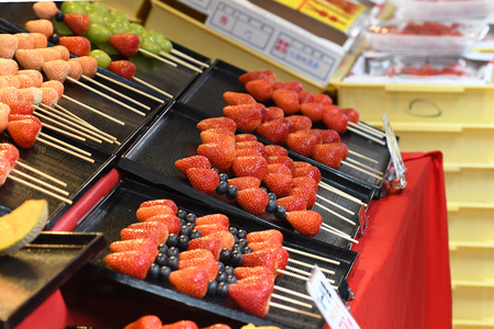 Tokyo, Japan - May 16, 2017: Fresh Strawberries on stick are sold along the street at Tsukiji fish market, Tokyo, Japan