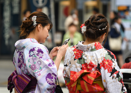 Tokyo, Japan - May 16, 2017: Women in Kimono are looking at their mobile phone along the street near Sensoji Temple, Tokyo, Japan
