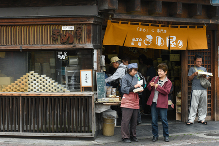 Kawagoe, Japan - May 14, 2017: Customer is tasting the local snack in front of the shop in Kawagoe, Japan