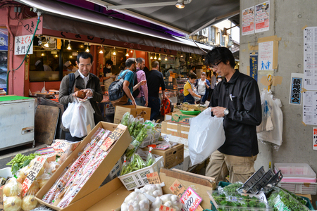 Tokyo, Japan - May 16, 2017: A man is selling variety of vegetables and fruit to his customer along the street at Tsukiji fish market, Tokyo, Japan