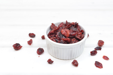 Dried cranberries in a bowl on white wood background Stock Photo
