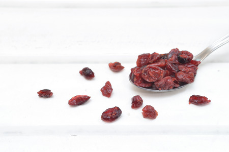 Dried cranberries in a spoon on white wood background