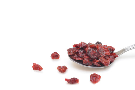 Dried cranberries in a spoon on white background - isolated Stock Photo