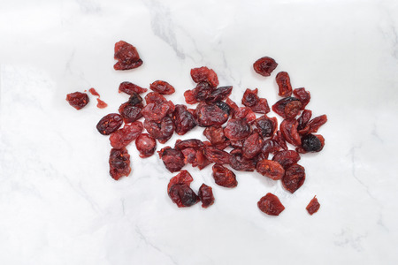 Dried cranberries on white marble background