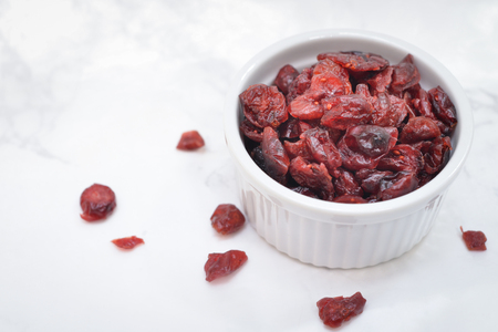 Dried cranberries in a bowl on white marble background Stock Photo