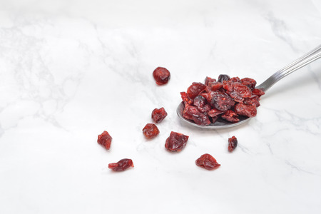 Dried cranberries in a spoon on white marble background